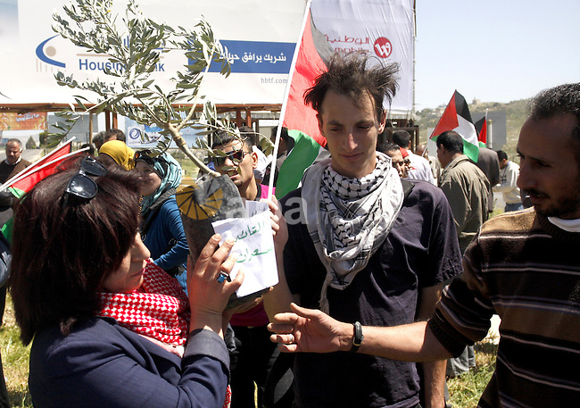 Palestinians and foreign activists hold Palestinian flag during a demonstration marking Palestinian Prisoners' Day ,in the Hawara checkpoint near the West Bank city of Nablus, Monday, April 16, 2012. Photo by Wagdi Eshtayah