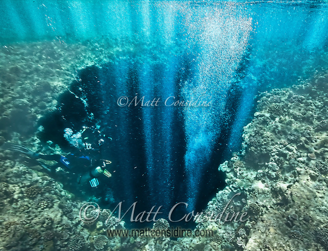 The divers' bubbles coming up through the hole in the top of the cave reflect the sunlight, Palau Micronesia. (Photo by Matt Considine - Images of Asia Collection)