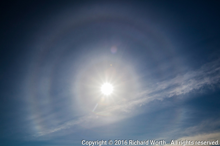 Ice crystals in the atmosphere create a halo around the sun over San Francisco Bay, seen from Crown Memorial State Beach in Alameda, California.