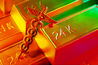 Pure gold bars (24K) and caduceus, symbol of physicians