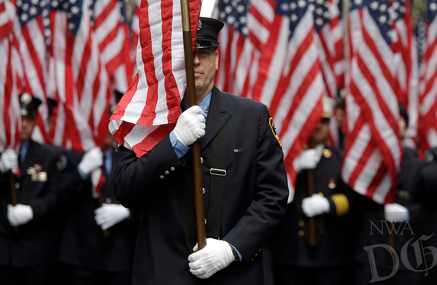 Firefighters carrying 343 American flags representing each of their colleagues who died during the terrorist attacks on the World Trade Center, march up Fifth Ave. during the St. Patrick's Day Parade, Tuesday, March 17, 2015, in New York.  (AP Photo/Mary Altaffer)