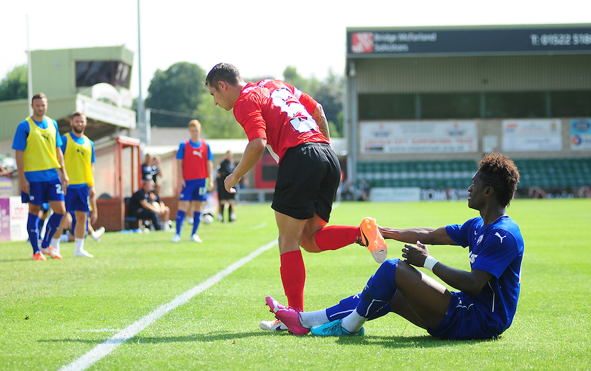 Chesterfield's Armand Gnawduellet holds on to the right ankle of Lincoln City's Ben Tomlinson preventing the Lincoln player from walking away from him<br /> <br /> Photographer Chris Vaughan/CameraSport<br /> <br /> Football - Friendly - Lincoln City v Chesterfield - Saturday 19th July 2014 - Sincil Bank Stadium - Lincoln<br /> <br /> &copy; CameraSport - 43 Linden Ave. Countesthorpe. Leicester. England. LE8 5PG - Tel: +44 (0) 116 277 4147 - admin@camerasport.com - www.camerasport.com