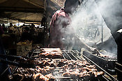 A man grills meat and fish at the organic farmers market in Sacedo Park in Makati, Manila in the Philippines. There is a surge in the demand for organic products to supply for people who can afford to pay extra.<br /> Photograph: Sanjit Das/Panos for Greenpeace