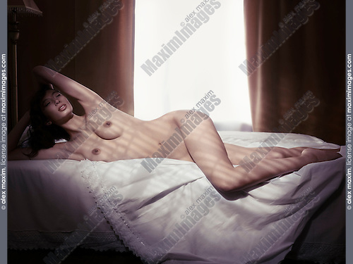 Artistic photo of a beautiful young woman lying naked on a bed in dim light