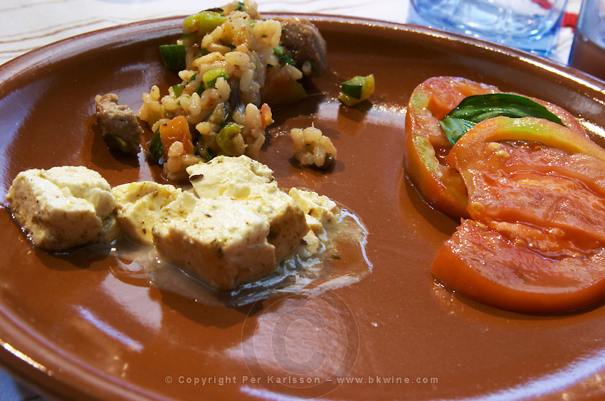 An earthenware plate with tomato and basil leaf salad, vegetable risotto, goat cheese from northern Albania Tradita traditional restaurant, Shkodra. Albania, Balkan, Europe.