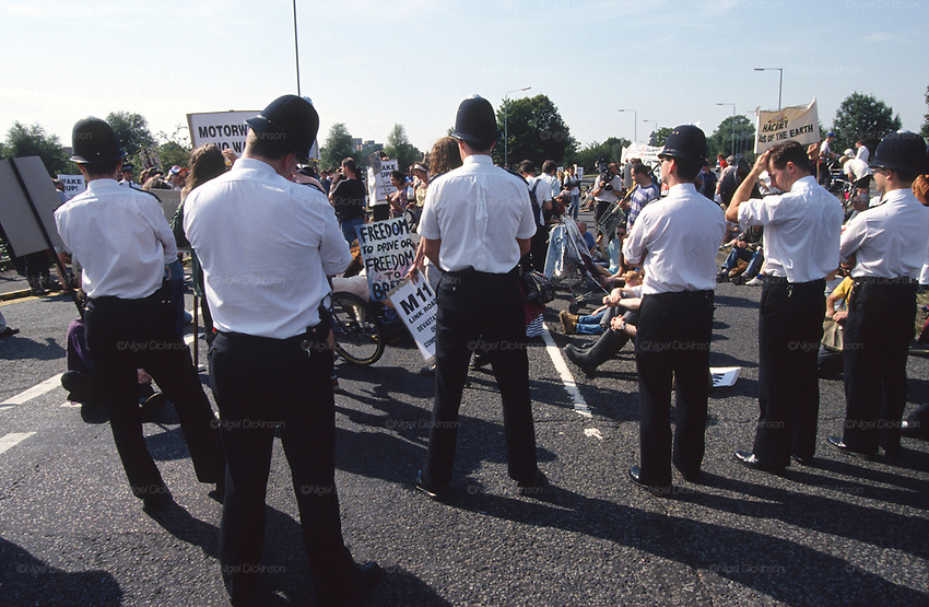 Road protesters occupy the path of the M11 link road during a mass protest. Road Protest site at George Green, Wanstead, London. The M11 link road protest was the start of a major anti-road protest in Wanstead and Leytonstone, in autumn 1993 opposing the construction of the M11 Link Road. It began with a protest to save the 250-year-old sweet chestnut tree that grew upon George Green. In winter of 1993 dozens of protesters occupied a house on George Green, Wanstead. In the early morning of 7 December 1993, several hundred police and bailiffs arrived to evict the protesters, which took a day hours to carry out.<br /><br />The British Road Protesters movement began in the early 1990s when the Donga tribe squatted Twyford Down to save this beautiful site, a site of scientific interest SSI from the Ministry of transport's road building programme which threatened to destroy the landscape. The Dongas was the name of the ancient walkways, the paths trodden in the middle ages by people walking down to Winchester. A small tribe were joined by people of all walks of life who came to Twyford Down to defend it. A long hard battle over several years ended in the 'cutting' a new motorway built through this ancient monument and destroying it. <br /><br />The Road Protest movement in Britain continued for many years and more battles were fought in London against the MII both at Wanstead then in Leytonstone, and subsequently at Newbury, and in Sussex. the protesters were very inventive in their use of non violent peaceful direct action. They barricaded themselves into squats, made tree houses, tunnels and have huge demonstrations against the bailliffs, police and security who tried to force their way through the defences of this alternative environmental popular movement. Many of the roads were built eventually and many sites of great beauty lost, but the government had to stand down from its road building policy and eventually the programme was halted. the protests cost the governm