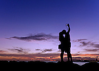 """A couple silhouetted at sunset takes a """"selfie"""" (self-portrait with a smartphone or camera) at sunset, O'ahu."""
