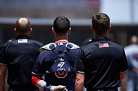 Umpires Bailey Dutten (left) and Jarrod Moehlmann (right) stand beside AZL Indians Blue catcher Michael Amditis (8) during the playing of the National Anthem before an Arizona League game against the AZL Indians Red on July 7, 2019 at the Cleveland Indians Spring Training Complex in Goodyear, Arizona. The AZL Indians Blue defeated the AZL Indians Red 5-4. (Zachary Lucy/Four Seam Images)