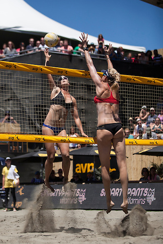 25.06.2016. San Francisco, California, USA.  Sara Hughes (left) attacks the ball as Kerri Walsh Jennings goes up for a block during the AVP San Francisco Open in San Francisco, CA.