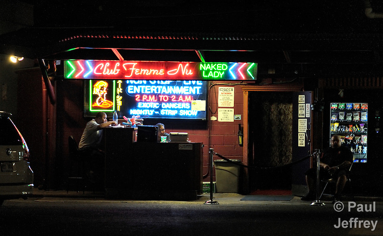 A night club in Honolulu, Hawaii, advertises nude performers.