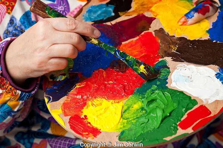Woman holding multicolored palette and paint knife while mixing paint while mixing paint