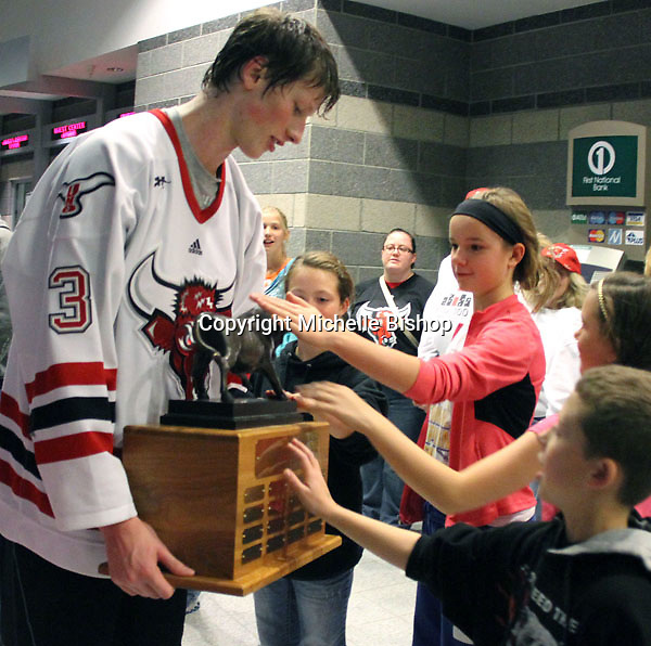 Young UNO fans touch the Spirit of the Maverick trophy as UNO's Zahn Raubenheimer holds it during post-game celebrations Saturday night. (Photo by Michelle Bishop)