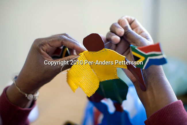 JOHANNESBURG, SOUTH AFRICA - MAY 10: An unidentified artist sews bed work on a Makarapa helmet on May 10, 2010, in Alfred Baloyi's studio in Wynberg, north of Johannesburg, South Africa. Mr. Baloyi, and a diehard Kaizer Chiefs soccer fan, started to make these hats in 1979. Initially he asked a friend who worked at a construction site for a helmet, as he wanted to protect himself from missiles at games. He later started to paint it, and later started to make this different figures hand cut out from the helmet. During the years he has made many different artistic hats that are on display in his studio in a shack in Primrose, Johannesburg. He later gave up his job as a washer of busses. From his small workshop in a squatter camp in Primrose south east of Johannesburg he recently made partner with an investor and have a brand new factory with about fifty people employed to make the hats. (Photo by Per-Anders Pettersson/Getty Images)