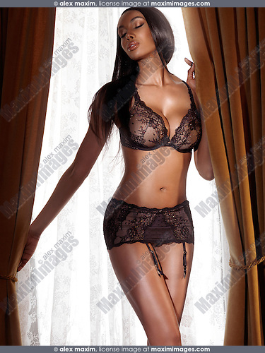 Glamour photo of a beautiful sexy black woman wearing lingerie standing in front of a window with closed eyes