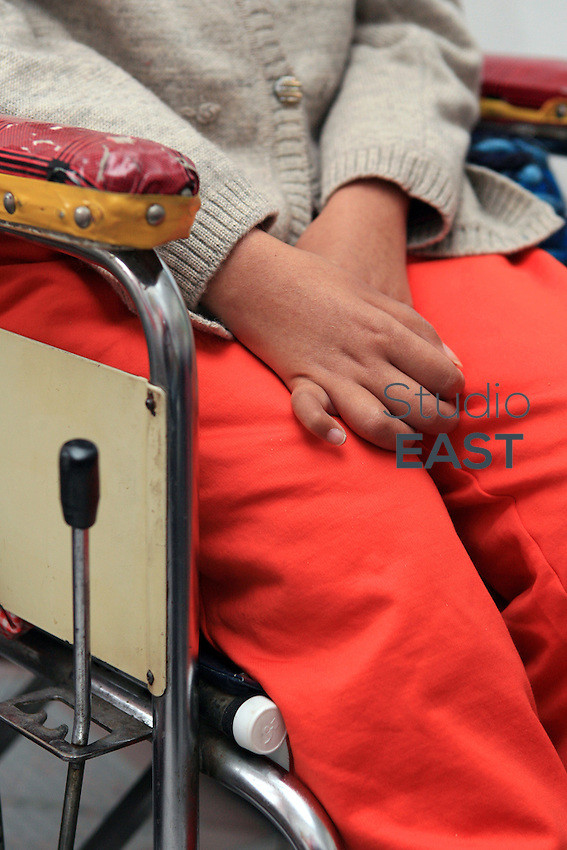 Li Yan's hands rest on her legs while she sits in her wheel-chair in her home in Yinchuan, Ningxia Province, China, on May 7, 2007. 28-year-old Li Yan suffers from motor neuron disease also known as amyotrophic lateral sclerosis (or ALS), the same illness that has thereotical physicist Stephen Hawking. Li Yan asked China's National People's Congress (NPC) to consider a draft on euthanasia. Photo by Lucas Schifres/Pictobank