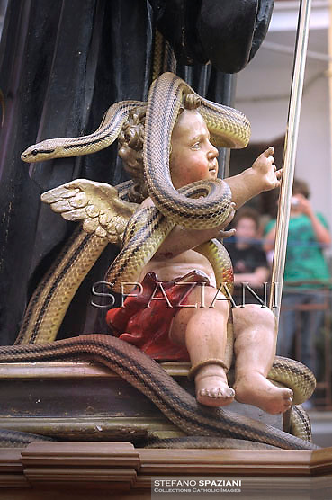 """Particular statue of Saint Domenico surrounded by live snakes is held up by worshippers during an annual procession dedicated to the saint, in the streets of Cocullo, in the Abruzzo region, on May 1, 2012...The St. Domenico's procession in Cocullo, central Italy. Every year on the first  of May, snakes are placed onto the statue of St. Domenico and then the statue is carried in a procession through the town. St. Domenico is believed to be the patron saint for people who have been bitten by snakes:..Italy, Cocullo, in the Province of L'A...quila, is at 870 meters a.s.l., along the railway line connecting Sulmona to Rome. The village rises alongside Mount Luparo (1327 meters) """"The valley opening in front of the village is surrounded by bare rocks, while on the other side, to the south, snow-capped mountain crests follow one after the other..."""".San Domenico Abate lived in the 10th and 11th centuries AD. Born in Foligno, in the Umbria region, he started his pilgrimages, preaching and ascetic practices in Central Italy, making miracles recorded by the word-of-mouth tradition. He died on 22 January 1031 and was buried in Sora...Cocullo snake charmers are over with their snake hunting. They proceeded through the During the procession on the first in May, before the snakes are placed all over the statue of St. Dominick, they will be fed with milk kept in containers with crusca. It is the snake that, most of all other elements, expresses an ancestral myth: the unknown aspect and unpredictability of the natural environment with man's innate need to achieve the dominance on his own habitat. ..Snakes and wolves were the emblems of Italic peoples like the Marsians and Irpinians. Some areas in Abruzzo, especially in the Sagittario valley, were under the menace of wolves and snakes, which for the local populations represented the uncertainty and anxiety of their existence that, together with the precariousness and hardships of life, were almost unbearable. Therefore the community"""