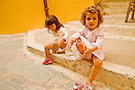 Two young Greek girls put on their shoes  in Chania, Crete.
