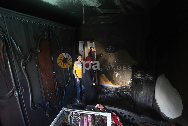 Palestinians inspect the damage in the bedroom of one-year-old Fathi Baghdadi, who died after a fire from a candle that swept through their home in the Bureij refugee camp in the center of the Gaza Strip on September 26, 2012. The Baghdadi family was using candles due to a power outage at the refugee camp. Cash-strapped Gaza has been suffering from a chronic energy crisis for years, exacerbated by an Israeli blockade of varying intensity imposed in 2006. Photo by Ashraf Amra
