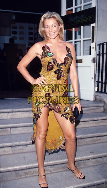 NELL MCANDREW..Ref: 10947..legs, cleavage, posing, model, split dress, full length, leaves..www.capitalpictures.com..sales@capitalpictures.com..