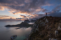 Female hiker watches midnight sun from summit of Offersøykammen mountain peak, Vestvågøy, Lofoten Islands, Norway