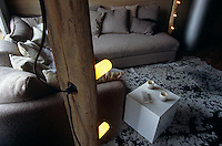 The sitting room has subdued lighting and is furnished with an L-shaped sofa stacked with cushions