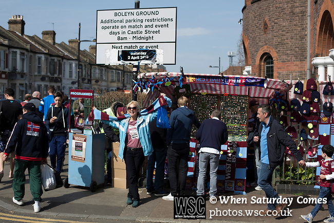 West Ham United 2 Crystal Palace 2, 02/04/2016. Boleyn Ground, Premier League. A woman poses for a photograph with her scarf aloft on the corner of Green Street and Castle Street near the Boleyn Ground before West Ham United hosted Crystal Palace in a Barclays Premier League match. The Boleyn Ground at Upton Park was the club's home ground from 1904 until the end of the 2015-16 season when they moved into the Olympic Stadium, built for the 2012 London games, at nearby Stratford. The match ended in a 2-2 draw, watched by a near-capacity crowd of 34,857. Photo by Colin McPherson.