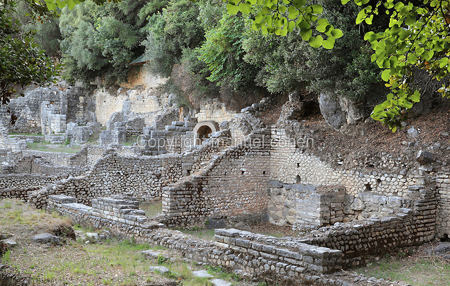 The Roman Forum, built after Julius Caesar's designation of Butrint as a Roman colony in 1st century BC, Butrint, Chaonia, Albania. The Forum is a monumental open space used for public life, business and worship. It had 3 shrines to the North, is surrounded by porticoes and has a stone pavement. It was discovered by archaeologists in 2005. Butrint was founded by the Greek Chaonian tribe and was a port throughout Hellenistic and Roman times, when it was known as Buthrotum. It was ruled by the Byzantines and the Venetians and finally abandoned in the Middle Ages. The ruins at Butrint were listed as a UNESCO World Heritage Site in 1992. Picture by Manuel Cohen