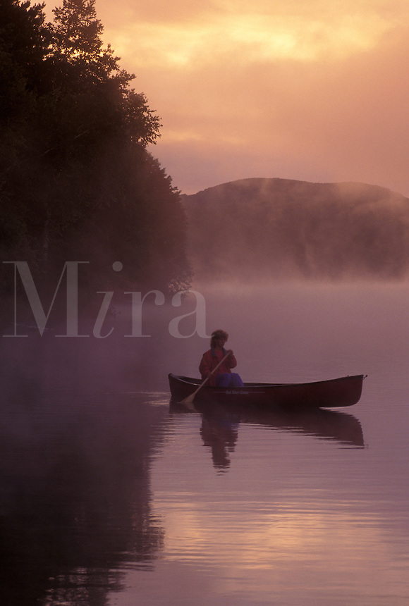 canoeing, canoe, sunrise, sunset, Vermont, VT, Woman paddling a canoe on Mollys Falls Pond at sunrise in the fog.