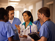 A doctor has a meeting with nurses in a hospital hallway in the middle of a long shift