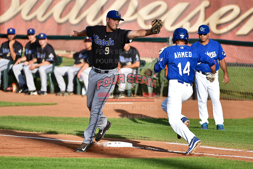 Missoula Osprey first baseman Trevor Mitsui (9) reaches for a wide throw as Michael Ahmed (14) of the Ogden Raptors hustles down the line in Pioneer League action at Lindquist Field on August 4, 2014 in Ogden, Utah.  (Stephen Smith/Four Seam Images)