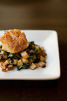 Scallop sitting on a bed of potatoes and spinach on a wooden table
