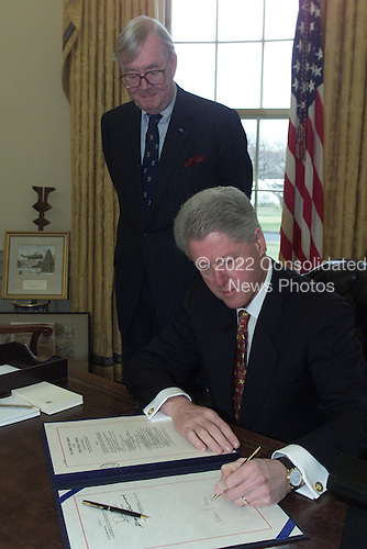 United States President Bill Clinton signs the Intelligence Authorization Act with U.S. Senator Daniel Patrick Moynihan (Democrat of New York) overlooking in the Oval Office of the White House in Washington, D.C. on December 27, 2000..Mandatory Credit: David Scull - The White House / CNP
