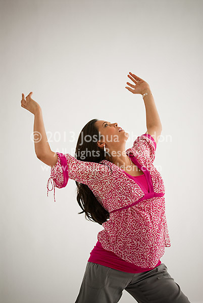 Pregnant Hispanic woman, arms reaching up in the air