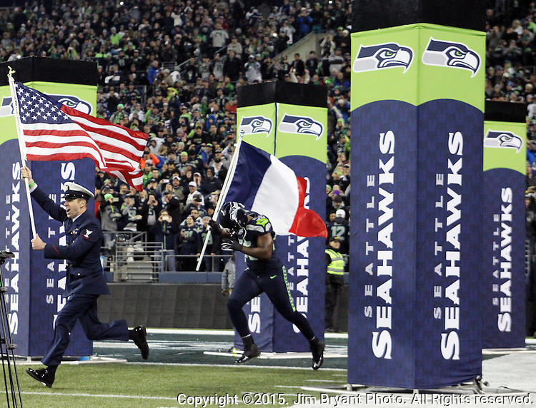 Aviation Survival Technician 2nd Class Darren Harrity brings the U.S. Flag out onto the field followed by Seattle Seahawks defensive end Cliff Avril, who carries the French Flag before their game against the Arizona Cardinals at CenturyLink Field in Seattle, Washington on November 15, 2015. The Cardinals beat the Seahawks 39-32.    ©2015. Jim Bryant photo. All Rights Reserved.