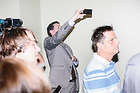 A news reporter uses his phone to take a picture of former Pennsylvania senator and Republican presidential candidate Rick Santorum after he spoke at a town hall event at the Concord office of New England College in Concord, New Hampshire.