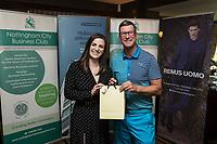 Denada Berisha of Remus Uomo gives a raffle prize to Gary Lund