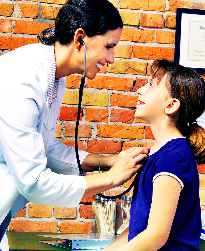 Female doctor treating a young girl with a stethocope and a smile.