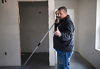 Sid Johnson, a licensed remodeler with Northwest Arkansas Floor Refinishing, stains and seals concrete floor, Thursday, January 9, 2019 at a new home being built on 508 S. Washburn Ave. in Fayetteville. <br /> <br /> Habitat for Humanity is building their 57th house in Washington County for their Women Build program. In the program, women from the community come together to raise money for the building of a new home and also help build it. 70 percent of the home must be built by women.  <br /> <br /> The house will go to a single mother and her son. Habitat has partnered with local businesses to help build the house like Sid Johnson of Northwest Arkansas Floor Refinishing.<br /> <br /> Habitat has worked on the house since July and expects to finish by march. Habitat is looking for week day volunteers to help with construction. <br /> <br /> Anyone interested in volunteering can sign up on givepulse.com found through habitatwashingtoncoar.org. This year, Habitat will roll out a new home repair program. People will be able to apply to have their homes repaired based on need, paid for by an interest-free loan the home-owner would pay back. Check out nwaonline.com/200110Daily/ for today's photo gallery.<br /> (NWA Democrat-Gazette/Charlie Kaijo)