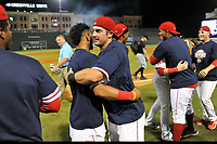 Greenville Drive players celebrate their 2017 South Atlantic League Championship, as league President Eric Krupa carries the trophy to the ceremony in the background following an 8-3 win over the Kannapolis Intimidators in Game 4 of the Championship Series on Friday, September 15, 2017, at Fluor Field at the West End in Greenville, South Carolina. It was Greenville's first SAL Championship. Greenville won the series 3-1. (Tom Priddy/Four Seam Images)