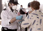 NOT MODEL RELEASED; FOR EDITORIAL USE ONLY... security guards wearing face masks at hospital in Toronto screen a woman entering the SARS assessment clinic