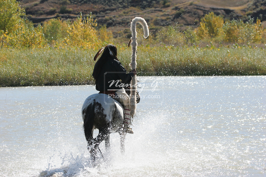A Native American Sioux Indian on horseback riding his pony across a river in South Dakota