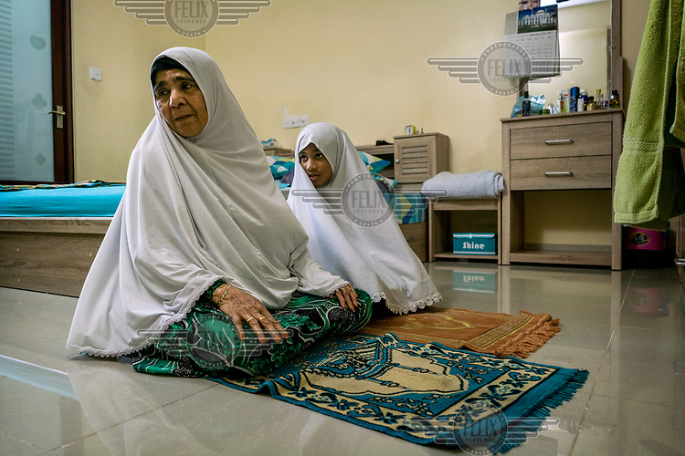 Aminath Eesa, 68, (left) the mother of disappeared journalist Ahmed Rilwan prays at home with her granddaughter (Rilwan's neice), Aishath Ainee Amir, seven.