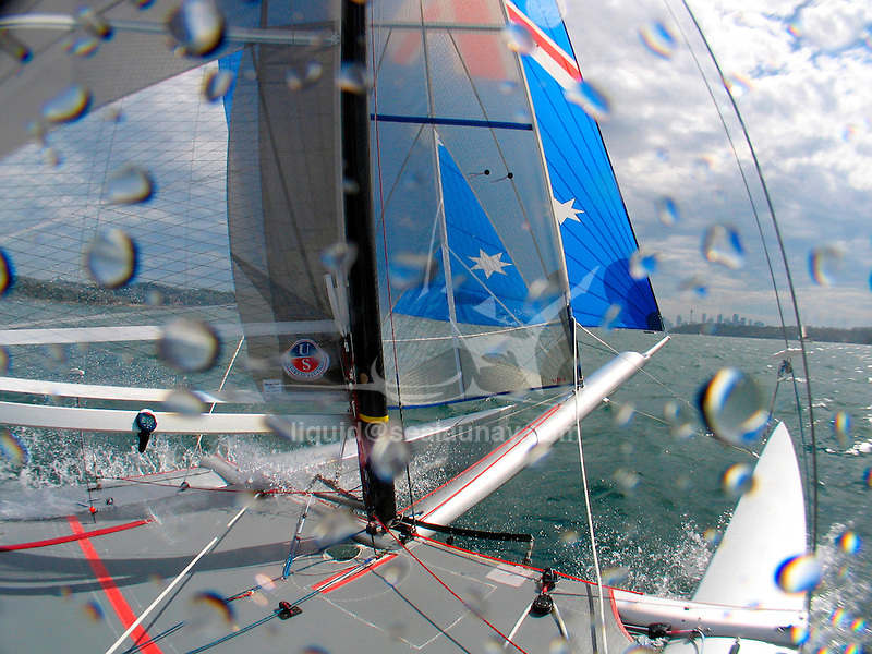 "Onboard a Tornado with the skipper Andrew Macpherson and crew Greg Lynch during a training session, Sydney Harbour..The Tornado is an olympic class sailing catamaran, with a crew of two. It was in the Olympic Games from 1976 through 2008, when multihulls were deselected for the 2012 games. It was designed in 1967 by Rodney March of Brightlingsea, England, with help from Terry Pierce, and Reg White, specifically for the purpose of becoming the Olympic catamaran. To increase its performance even further, the Tornado was modified in 2000, with a new sail-plan which included a Spinnaker and Spinnaker boom, as well as an increased sail area of the existing sails. An additional trapeze was also added, and the jib was made self tacking..The Tornado typically flies one of its two hulls; the crew balancing the boat with their own weight and by controlling the sails. With only one hull in the water, drag is significantly reduced. The Tornado also features an adjustable, rotating mast, which not only greatly improves the aerodynamics of the crucial leading edge of the sail, but also allows improved control over mast bend and thus mainsail flatness. For the high speeds and apparent wind directions seen by this high speed vessel, a flat sail profile is often required..The Tornado is said to be capable of speeds above 30 knots (56 km/h) reaching, and 18 knots (33 km/h) upwind, the Tornado class is often characterized as ""the Formula One of sailing""."