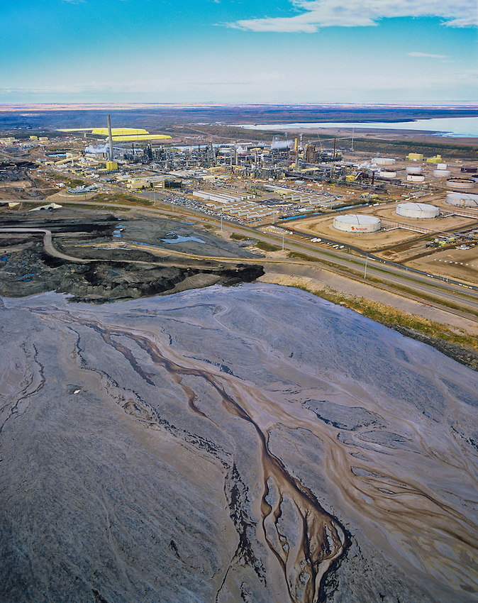 Syncrude Operations..Alberta Oil Sands and effluent pond. Northern Alberta.                 .The toxic effluent ponds of the alberta Tar Sands are so large that they can be seen from outer space.  Every barrel of oil requires 3-5 barrels of fresh water to refine. This is dramatically reducing water levels in the Athabasca River and threatening the Athabasca Delta, one of the World's greatest inland deltas and critical habitat for birdlife.                    These oil reserves are second only to those of Saudi Arabia. Their method of extraction is among the most damaging and their refining creates more greenhouse gases than any other oil refining process..Copyright Garth Lenz. Contact:  lenz@islandnet.com www.garthlenz.com