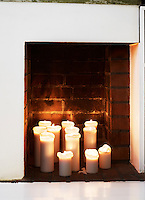 An arrangement of candles in the fireplace recess in the bedroom