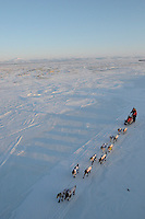 Iditarod sled dogs and musher Aliy Zirkle pass along Unalakleet River on a clear winter day towards Nome, Alaska, 2010