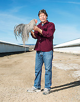 "President of Whiting Farms Thomas Whiting holds a Whiting ""dry fly hackle"" rooster, in Delta, Colorado, Wednesday, March 16, 2016. The feathers are used to tie dry flies for fly fishing. The specific structure and characteristics of the hackle feathers allow the fishing fly to ride on top of the meniscus of the water like an insect. The rooster's color or pattern is known in the fly tying world as a ""grizzly"". In the background are two rooster sheds, each of which are 420 feet long.<br /> <br /> Photo by Matt Nager"
