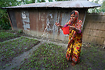 Kuriful waters her home garden in Kunderpara, a village on an island in the Brahmaputra River in northern Bangladesh. Severe flooding in August 2017 destroyed the island's crops but ICCO Cooperation, a member of the ACT Alliance, provided emergency food and seeds so that Kuriful (who uses only one name) and other islanders could replant their food crops and restart their lives.
