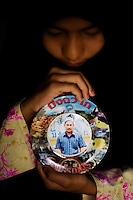 13 year old Daliah Masae grieves over her murdered father, Gayo Masae, who was shot on the steps of his mosque in Talok Ao village, Pattani. She holds a plate with his photograph that was presented to his family at a workshop for imams organised by the government. He is now the fourth imam who attended the workshop to have been killed. The insurgency in Southern Thailand began as a conflict between the Malay muslim population and central government, but now the boundaries have become blurred and various guerilla groups have become involved. No-one seems certain as to who is fighting who. As of March 2008, the insurgency had claimed as many as 3,000 lives.