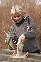 Kind füllt Vogel-Futterhäuschen mit Spezial-Fettfutter, Energieblock, Futterhaus, Futterhäuschen, Vogelfutter